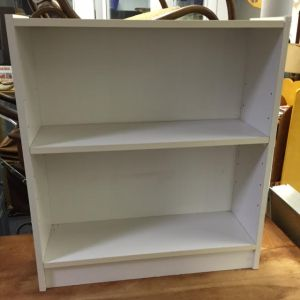 """Small White Bookcase. About 25""""W x 27.75""""H x 8""""D. Our Price: $22.00."""